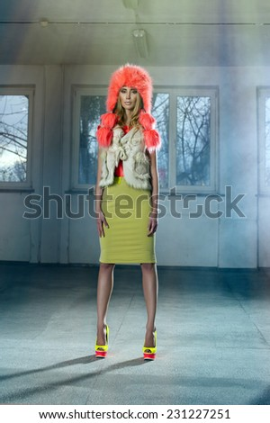 Sexy woman in fluorescent clothes posing in empty hall