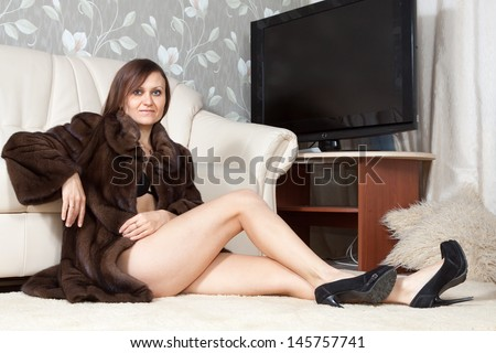 Sexy woman in fur coat  at home interior - stock photo