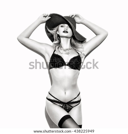 Sexy woman in hat and underwear posing at wall, black and white - stock photo