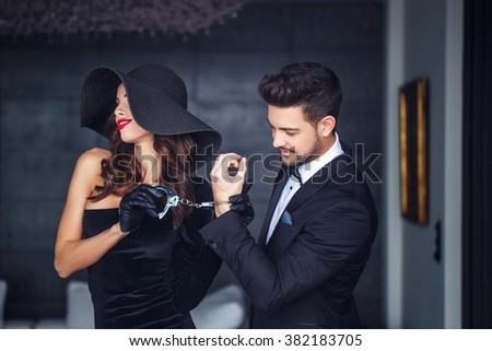 Sexy woman in hat holding young rich lover on handcuffs indoor, teeth smile - stock photo