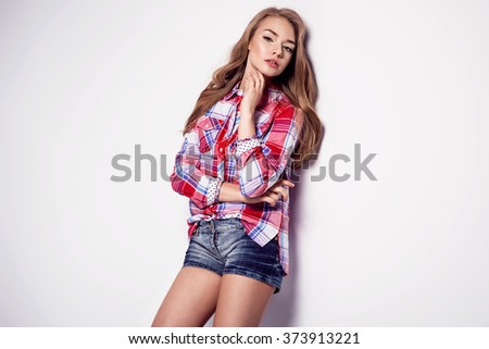 Sexy woman in jeans shorts, checked shirt posing on white background. Summer fashion photo. Fitness body - stock photo