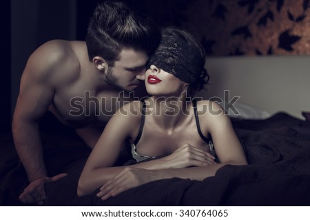Sexy woman in lace eye cover and red lips with young lover, foreplay in hotel room