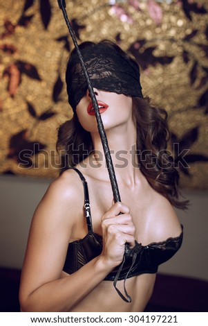 Sexy woman in lace eye cover holding whip, bdsm - stock photo