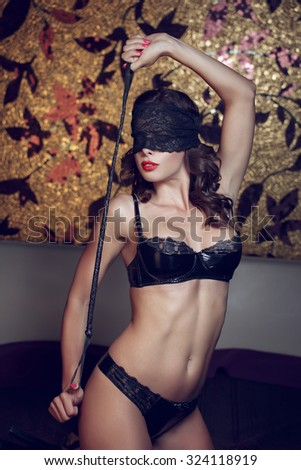 Sexy woman in lace eye cover holding whip, kneeling on bed, bdsm - stock photo