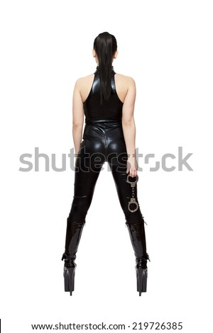 Sexy woman in latex catsuit and high heels boots holding handcuffs, isolated on white, bdsm - stock photo