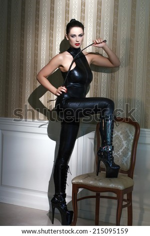 Sexy woman in latex catsuit with whip step on chair, desire - stock photo