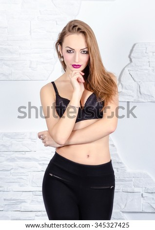 Sexy woman in leggins and bra. Indoor studio shot. - stock photo