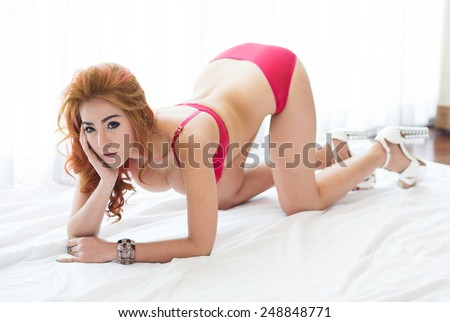 Sexy woman in lingerie lying on the floor in bedroom - stock photo