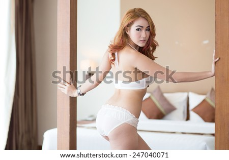 Sexy woman in lingerie posing on the sofa in bedroom - stock photo