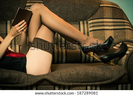 sexy woman in lingerie reding on a sofa - stock photo
