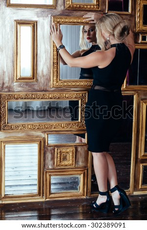 Sexy woman in little black dress posing near mirrors. fashion photo