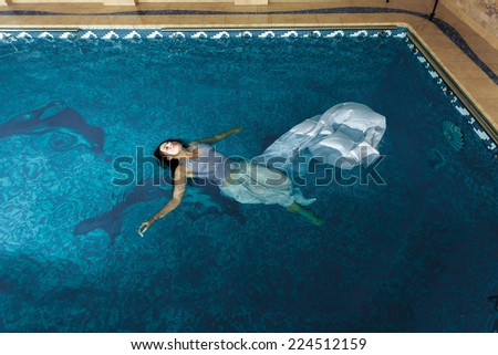Sexy woman in long white dress swimming on water surface at swimming pool - stock photo