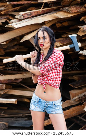 sexy woman in plaid shirt with axe - stock photo