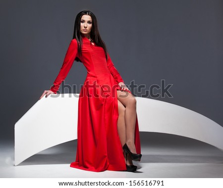 Sexy woman in red dress posing in studio - stock photo