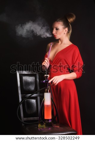 Sexy woman in red dress smoking hookah - stock photo