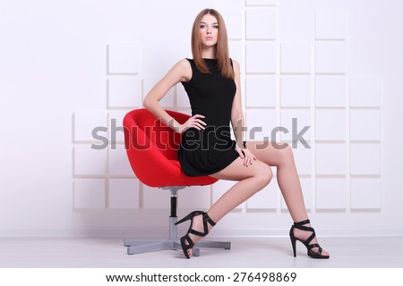 Sexy woman in short black dress sitting on a chair. Fashion shot