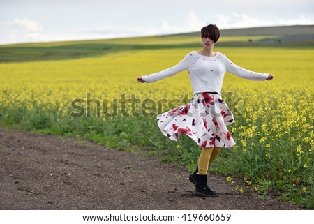 Sexy woman in skirt dancing near a canola field - stock photo