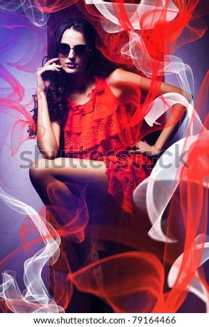 sexy woman in sunglasses and red dress around red and white fabric - stock photo