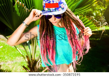 Sexy woman in sunglasses,white t-shirt.Swag style girl,cap and pink dreadlocks,tropical background,not isolated,lifestyle portrait,wearing bright swag style bra,having fun and make crazy funny faces - stock photo