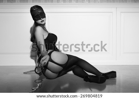 Sexy woman in underwear and lace eye cover with handcuffs posing on floor, black and white, bdsm - stock photo