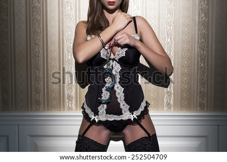 Sexy woman in underwear locking handcuffs at vintage wall - stock photo