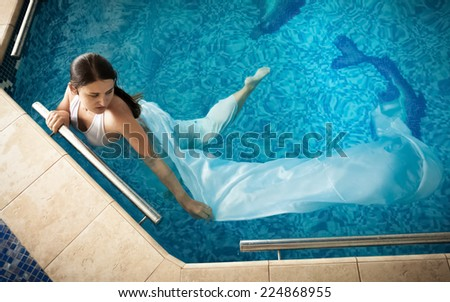 Sexy woman in white dress swimming next to edge in swimming pool - stock photo