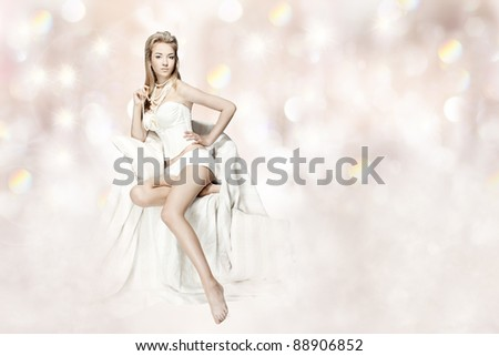 Sexy woman in white lingerie sitting in chair over abstract background - stock photo
