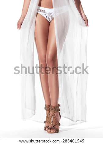Sexy woman in white sheer beachwear robe and bikini closeup of legs in sandals isolated on white background - stock photo