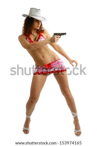 Sexy woman is bending and aiming a pistol. Her slender legs on high heels are stood apart. She is wearing white stetson, very short skirt and top decorated red bowls. Reclined body isolated on white. - stock photo