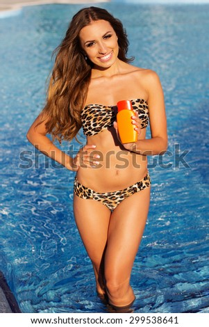 Sexy woman is resting near swimming pool with blue water holding orange jar with lotion in her hands, summer time