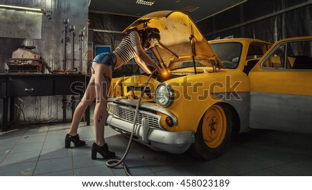 Sexy woman is welding something inside an old car.