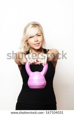 sexy woman keeping fit using a kettlebell weight to train with - stock photo
