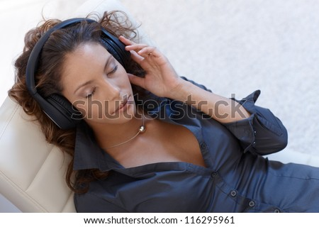 Sexy woman listening to music through headphones, eyes closed, view from above.