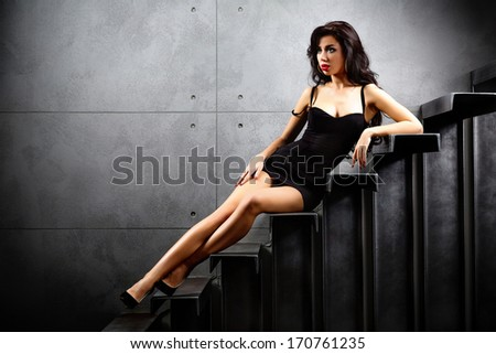 sexy woman lying on stairs at backyard of building - stock photo