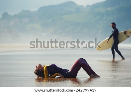 Sexy woman lying on wet suit with beautiful professional surfer on background, young surfer looking to the girl while walk to the ocean - stock photo