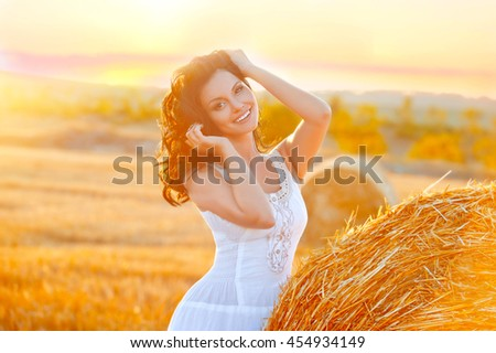 Sexy woman on hay stack on sunset. Beauty romantic girl outdoors against hay stack. Photo of sexy brunette in a field with haystacks - stock photo