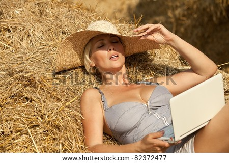 Sexy woman on laptop in hay stack on a summer day - stock photo