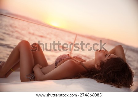 Sexy woman on sailboat lying down on the deck of luxury sailboat, tanning on mild sunset light, enjoying sea cruise, fashion and summer holidays concept - stock photo