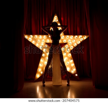 Sexy woman on stage.Red velvet curtain with brodway star on background  - stock photo