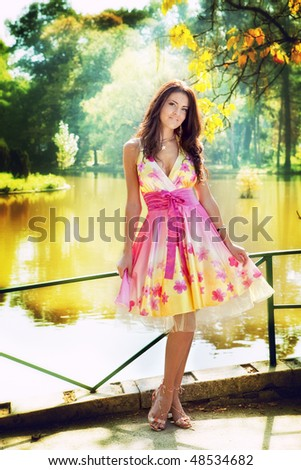 Sexy woman outdoor with nice colorful dress - stock photo