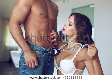 Sexy woman playing with macho lover in luxury flat - stock photo