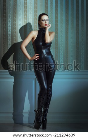 Sexy woman posing in latex catsuit and high heel boots at vintage wall - stock photo