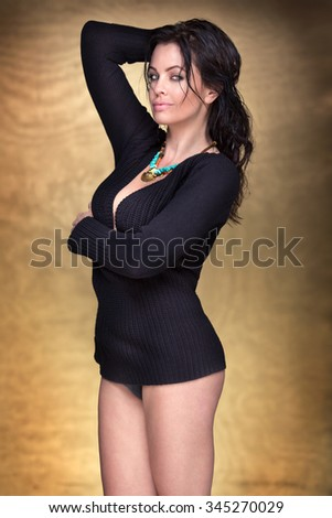 Sexy woman posing in studio on gold background, looking at camera. Sensual style. - stock photo