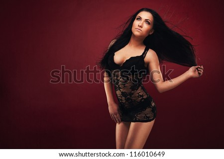 Sexy woman posing on the ground in studio - stock photo