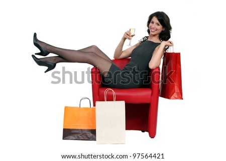 Sexy woman posing with her shopping bags and drinking a glass of wine - stock photo