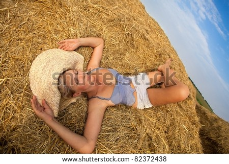 Sexy woman relaxing in hay stack on a summer day - stock photo
