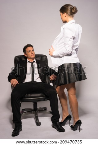 Sexy Woman Showing Off Body to Young Handsome Boss, Isolated on Gray Background. Emphasizing Seduction to Manager While Sitting on Chair - stock photo