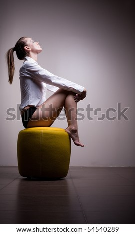 Sexy woman sitting alone in contemplation - stock photo