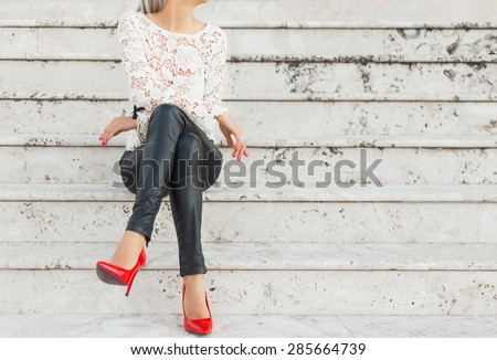 Sexy woman sitting alone on stairs - stock photo