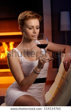 Sexy woman sitting in cosy room, enjoying smelling glass of wine. - stock photo